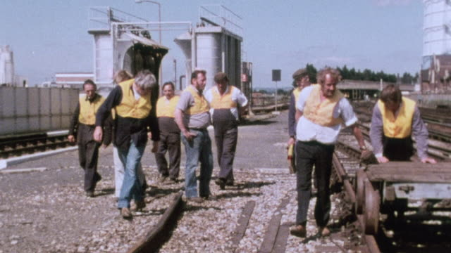 ts crew working on moving a trolley track using a long crowbar / united kingdom - 1980 stock videos and b-roll footage