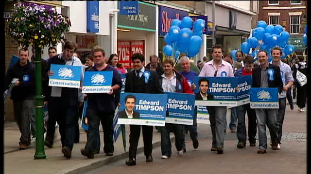 crewe and nantwich by-election: conservative victory; england: cheshire: crewe: ext conservative supporters along with banners and balloons following... - nantwich stock-videos und b-roll-filmmaterial