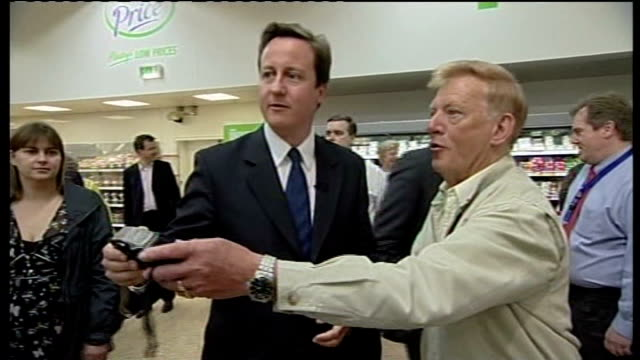 crewe and nantwich by-election; lib england: cheshire: crewe: int david cameron mp helping man take photograph in asda supermarket ext cameron and... - nantwich stock-videos und b-roll-filmmaterial