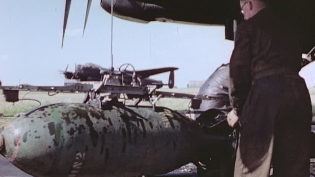 crewman locking hydraulic lift onto bomb and bomb rising into bay of parked lancaster heavy bomber - beladen stock-videos und b-roll-filmmaterial