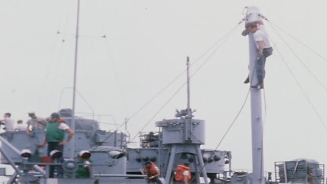 vídeos de stock, filmes e b-roll de crewmen on deck of uss harnett county preparing high line on mast crew members on deck hauling in line from uss regulus and high line speeding across... - formato letterbox