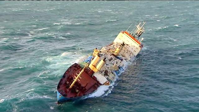 vídeos de stock, filmes e b-roll de crewmen rescued from listing cargo ship off devon coast; england: devon: ext air views ship 'ice prince' listing in water - enviesado