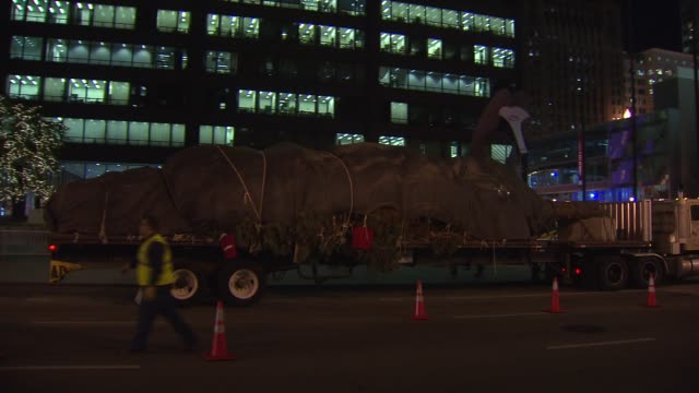 crews set up a colorado spruce for the 100th tree lighting ceremony in daley plaza truck carrying christmas tree drives down street at daley plaza on... - christmas tree lighting ceremony stock videos & royalty-free footage