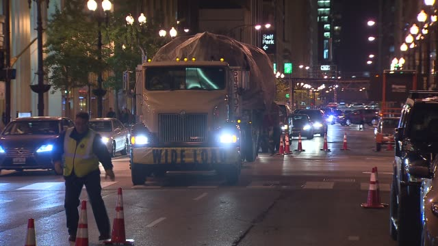 crews set up a colorado spruce for the 100th tree lighting ceremony in daley plaza truck carrying christmas tree drives down street at daley plaza on... - クリスマスツリー点灯式点の映像素材/bロール