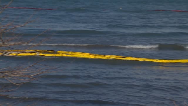 Crews setting up a containment boom in Lake Michigan to keep oil from spreading Between nine and 18 barrels of crude oil spilled into Lake Michigan...