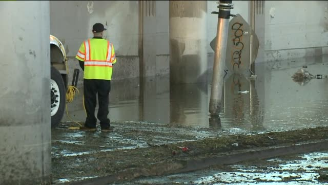 crews were vacuuming up water under the i-70 bridge at brighton blvd. and york street in denver on june 8, 2015 after fast moving storms moved... - 密閉点の映像素材/bロール