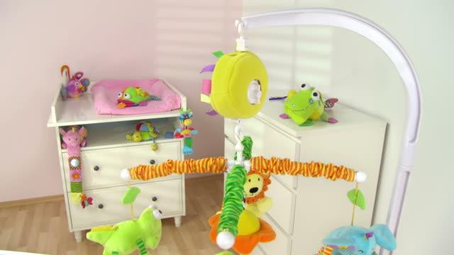 vídeos de stock, filmes e b-roll de hd: berço toy rodopiantes em belas sala de berçário - animal de brinquedo
