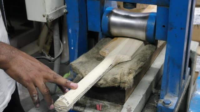 a cricket bat receiving its final pressing at a manufacturing unit in india - クリケットバット点の映像素材/bロール