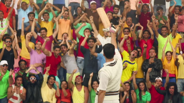 cricket batsman celebrating in front of spectators, delhi, india - cricket video stock e b–roll
