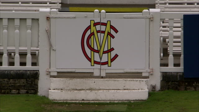 a cricket emblem hangs on a gate at the lord's cricket ground in london. available in hd. - lords cricket ground stock videos and b-roll footage