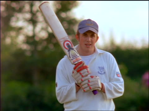 portrait cricket player in baseball cap holding bat + looking at camera / england - baseball cap stock videos & royalty-free footage