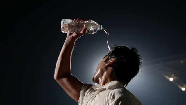 Cricket player throwing water in his face, Delhi, India