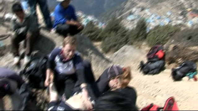 cricket team's mount everest mission day two members of treck team race eachother up path carrying loads cheered on by colleagues medical team tend... - cricket team stock videos and b-roll footage