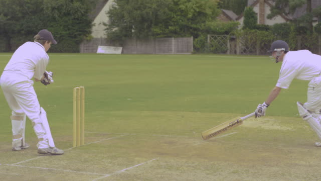 Cricket: Wicket keeper attempts to run out batsman but fails to hit stumps in time. Batsman is not out.