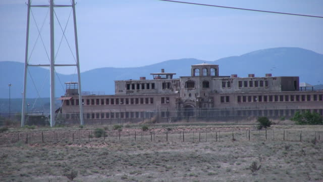 (hd1080i) crime: abandoned prison in barren desert, zoom out - federal prison building stock videos & royalty-free footage