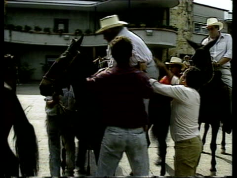 Drugs Baron Interviewed COLOMBIA Nr Medellin Ochoa's Ranch BV Don Fabio Ochoa drug baron being helped on to horse by aides CMS Ochoa riding along...