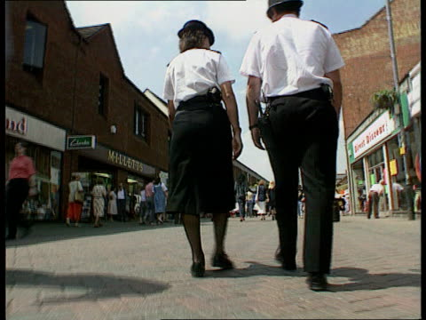 Police Racial Discrimination Legislation LIB Policeman and woman along thru town centre walking the beat