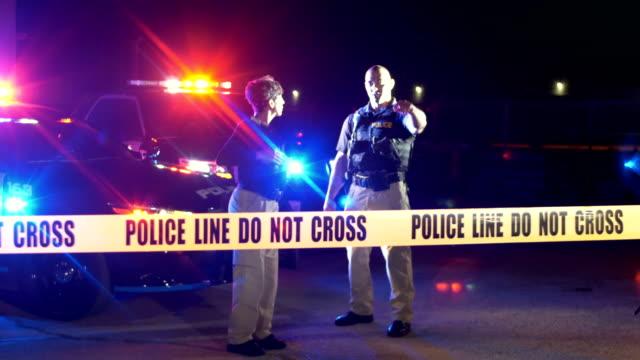 vidéos et rushes de scène de crime la nuit, policiers derrière la bande de cordon - crimes et délits