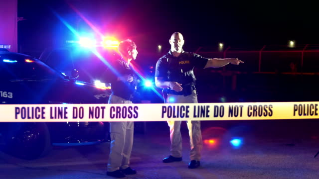 crime scene at night, police officers behind cordon tape - police vehicle lighting stock videos & royalty-free footage