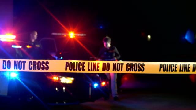 stockvideo's en b-roll-footage met plaats delict 's nachts, politieagenten achter cordon tape - afzetlint