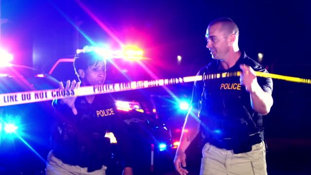 vidéos et rushes de scène de crime la nuit, la police marche sous le ruban adhésif de cordon - crime