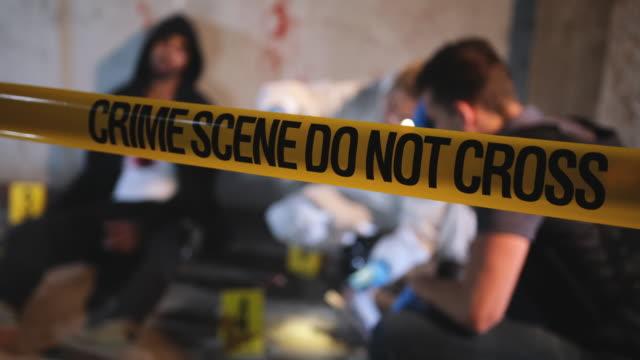 crime scene cordon tape and examination of murder victim - murder victim stock videos & royalty-free footage