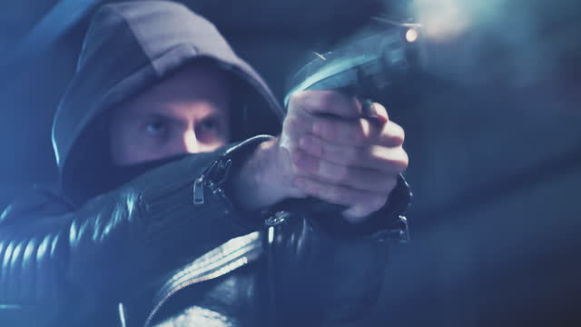 tatort. maskierter mann schießt handfeuerwaffe in der dunkelheit - torschuss stock-videos und b-roll-filmmaterial
