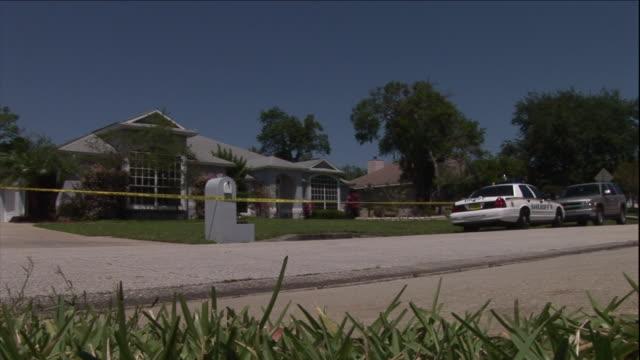 stockvideo's en b-roll-footage met crime scene tape surrounds a house. - afzetlint