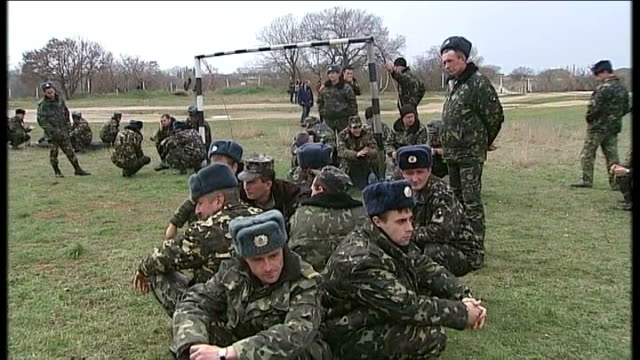 vídeos de stock e filmes b-roll de first shots fired at military base / international diplomacy; ukrainian soldiers reporter to camera and commander mamchur walking over to russian... - ucrânia bandeira