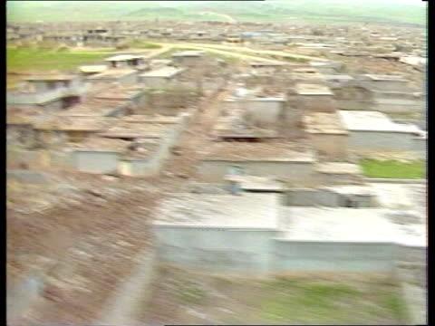 kurd massacres; crime/conflict: kurd massacres; ext iran/iraq a/g damaged buildings tx 22.3.88 border settlement?) covered with rubble ) itn halabja... - 大量殺人点の映像素材/bロール