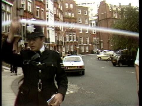 CrimeL London Murder ENGLAND London Knightsbridge 54 Hans Pl MS Police car RL past cordon LMS Police outside building PULL OUT policeman signalling...