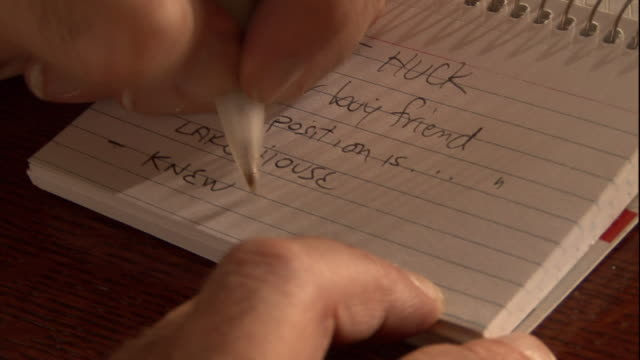 A criminal investigator jots down notes.