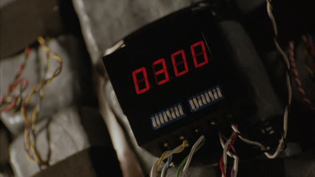A criminal pushes buttons on a bomb timer.