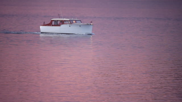a cris craft boat plies the calm waters of puget sound, washington at sunset. - puget sound stock videos & royalty-free footage