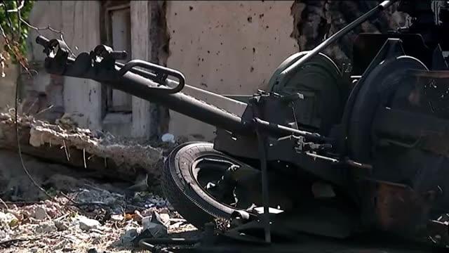 fighting in Ilovaysk Wreckage of burntout Ukrainian Army field gun Reporter to camera Wrecked Ukrainian Army truck at roadside shell embedded in road...