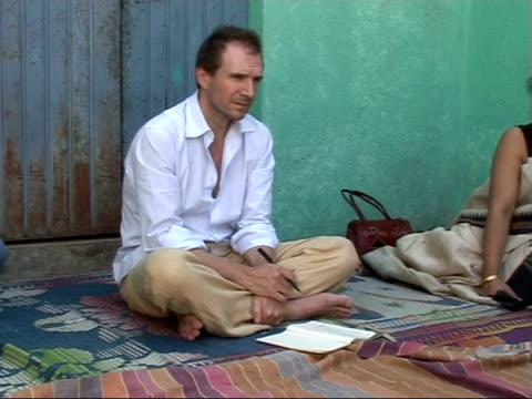 vídeos de stock e filmes b-roll de ralph fiennes visit: meeting villagers in maharashtra region / slums in mumbai; fiennes taking notes during meeting with local indian people / dome... - retrovírus
