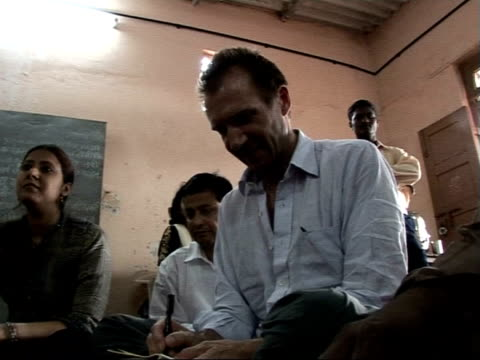 vídeos de stock e filmes b-roll de ralph fiennes visit: meeting villagers in maharashtra region / slums in mumbai; fiennes in meeting with local people ext young boy watching from... - retrovírus