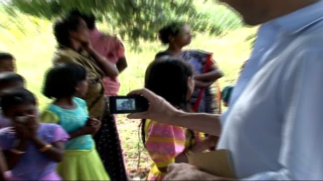 vídeos de stock e filmes b-roll de ralph fiennes visits aids sufferers; jiwali: fiennes chatting to children and showing them digital camera - retrovírus