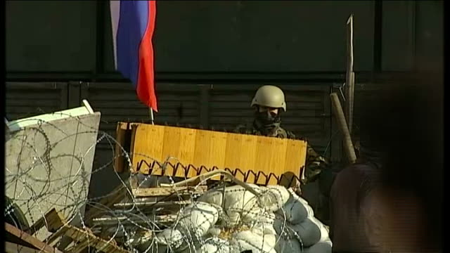 Russian troops move into more east Ukrainian towns Man raising Russian flag and removing Ukrainian flag Men marching along with Russian flag Reporter...