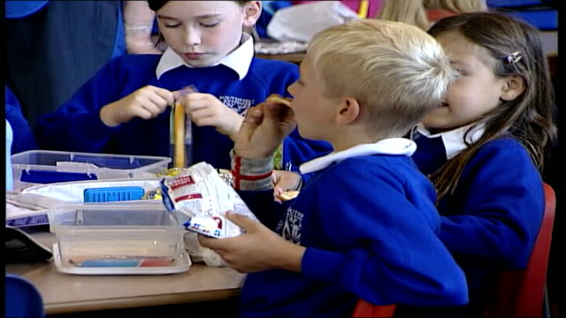 crisps fat warning; file / date unknown location unknown: int primary schoolchildren eating crisps at lunchtime - snack stock videos & royalty-free footage