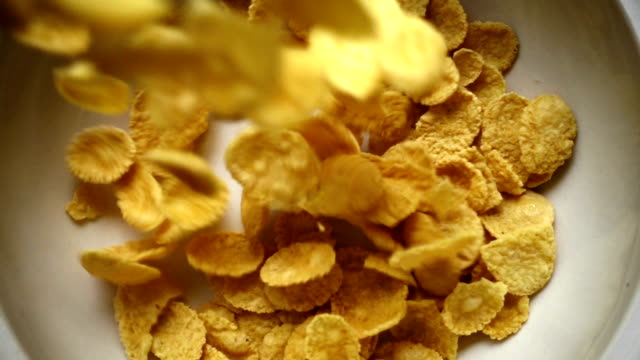 slo mo - crispy yellow cereal poured into the bowl - breakfast cereal stock videos and b-roll footage
