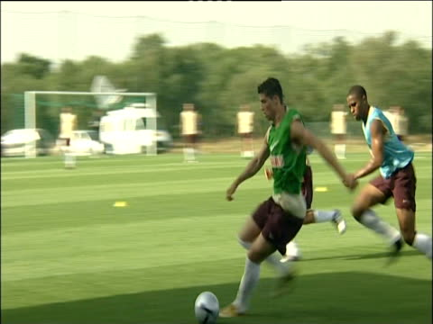 Cristiano Ronaldo turns and dribbles ball whilst tackled during Portugal football training session 10 Jun 04