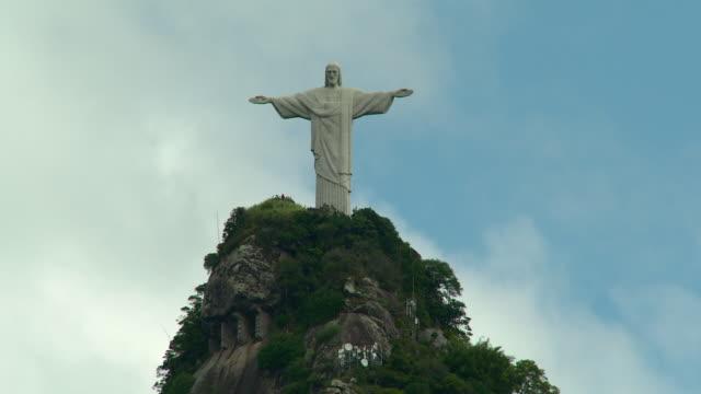 vidéos et rushes de cristo redentor statue on mount corcovado summit, mountain peak, blue sky w/ white clouds bg. - corcovado