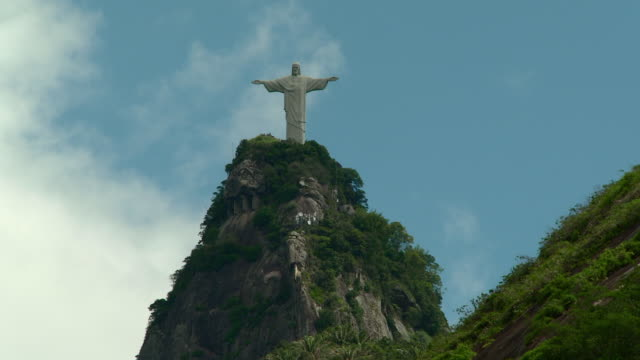 Cristo Redentor statue on Mount Corcovado summit mountain peak blue sky w/ white clouds BG