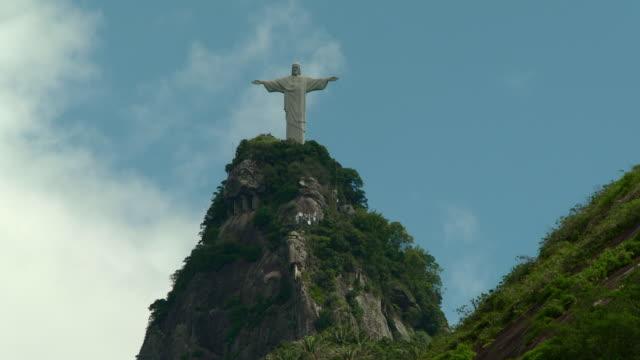 vidéos et rushes de cristo redentor statue on mount corcovado summit, mountain peak. blue sky w/ white clouds bg. - corcovado