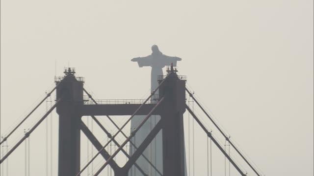 aerial ws zo cristo rei monument with april 25th bridge over tagus / lisbon, portugal - 4月25日橋点の映像素材/bロール