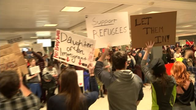 criticism of donald trump's immigration ban continues dulles international airport int protesters with 'support refugees' and 'let them in' placards... - dulles international airport stock videos and b-roll footage