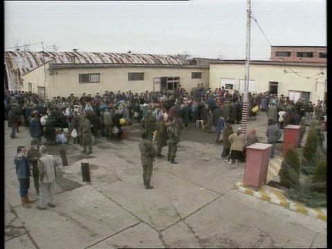 aid c4n yugoslavia croatia vukovar tgv mass of people in army camp compound ms people as woman hugs and kisses another ms federal soldier leading... - 旧ユーゴスラビア点の映像素材/bロール
