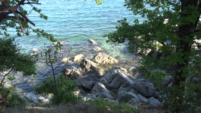 vídeos de stock, filmes e b-roll de croatia looking down at rocks on coast at high tide zooms - vazante
