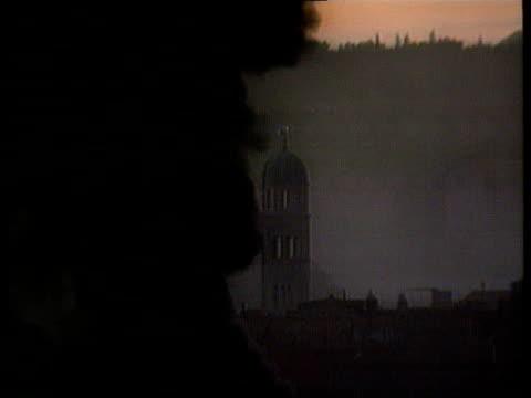 split david chater wounded yugoslavia croatia dubrovnik sunset cms thick column of black smoke and monastery tower in b/g ms columns of thick black... - 旧ユーゴスラビア点の映像素材/bロール